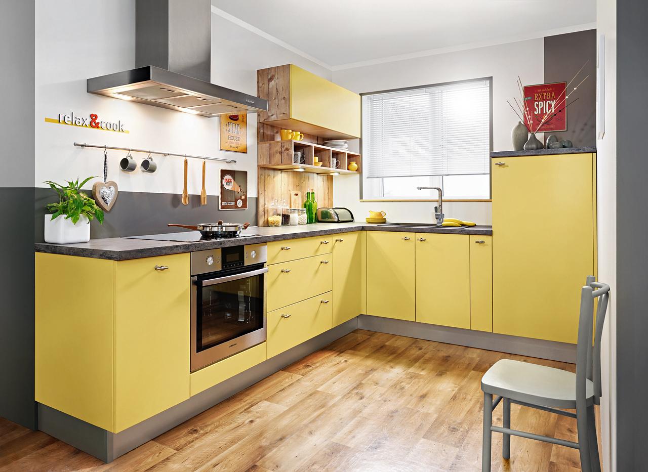 Mały, zgrabny zestaw idealny do niewielkiej kuchni. Fronty w nowym odcieniu szafranowym uzupełniają oryginalne uchwyty. Pozbawiona ich szafka górna otwiera się na dotyk dzięki elektrycznemu podnośnikowi Aventos. Fot. KAM
