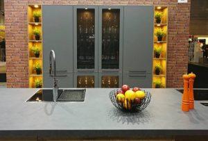 Szklana witryna usytuowana w centrum kuchennej zabudowy to jedno z najmodniejszych rozwiązań aranżacyjnych w tym sezonie. Fot. KAM
