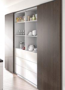 Coraz częściej szafa z drzwiami przesuwnymi jest projektowana w zabudowie kuchennej. Może pomieścić więcej niż zwykłe szafki i nie wymaga dodatkowego miejsca do otwarcia frontów. Dzięki systemowi TopLine można zaprojektować w jej wnętrzu wygodne szuflady i zachować modne, minimalistyczne płaszczyzny frontów bez uchwytów. Fot. Hettich