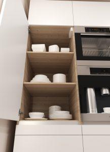 Coraz częściej kuchnia jest połączona ze strefą dzienną, a to wymaga niezwykłej staranności w doborze zabudowy meblowej. Otwarty front mebla powinien wyeksponować jego estetyczne wnętrze. Warto tu o element zaskoczenia - za białym frontem można ukryć półki uszlachetnione dekorem drewna. Fot. Hettich
