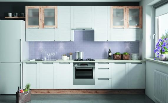 Bielone drewno frontów systemu Olivia Soft współgra z białą lodówką, dzięki czemu zaoszczędzono na szafce pod jej zabudowę. Mocny akcent w postaci eleganckiego srebrnego piekarnika podkreśla symetrię zabudowy. Taka aranżacja wprowadza ład i porządek w kuchni. Fot. KAM