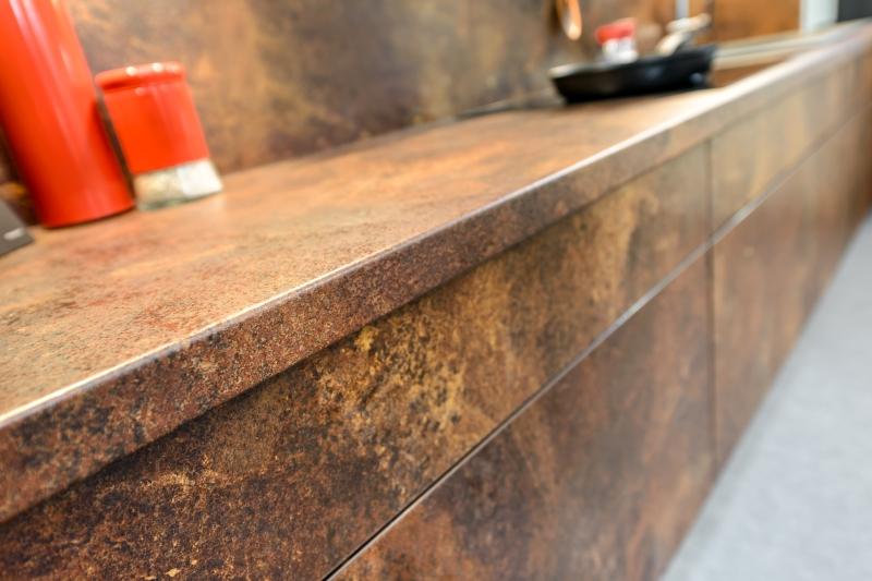 Jedną z ubiegłorocznych nowości, jaką KAM zaproponował klientom, był dekor rdzawy ceramic. Wykonany z niego blat (linia KAMplus) wygląda imponująco. Ciekawym zabiegiem jest wykończenie ściany nad blatem oraz wybranych boków i frontów mebli tym samym dekorem. Fot. KAM