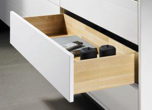 Piękno drewnianych szuflad wspomagane jest prestiżowym systemem prowadnic Quadro, które w niewidoczny sposób dbają o komfortowe otwieranie i zamykanie. Fot. Hettich