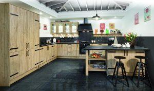 Dodatkowy blat roboczy z jednej strony, z drugiej ? wygodne miejsce do spożywania posiłków. Półwysep kuchenny w stylizowanej kuchni Kamelia z linii KAMPlus oddziela strefę kuchenną od salonu i dodatkowo może pełnić funkcję stołu. Fot. KAM