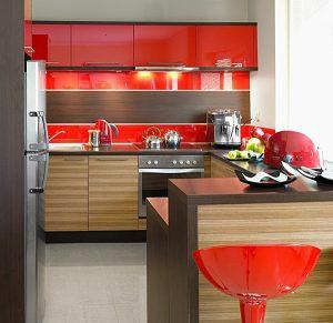 """Energetyczna czerwień w towarzystwie drewna to udany sposób na podniesienie atmosfery w kuchni. Intensywny kolor na pewno zwraca uwagę, jednak dzięki oprawie drewna kompozycja z linii KAM Plus nie wydaje się zbyt """"krzykliwa"""".  Fot. KAM"""