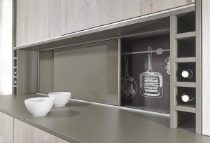 Z czasem w naszych kuchniach przybywa przedmiotów, a miejsca w szafkach nie. Zamiast ustawiać je na blacie, lepiej zaaranżować dodatkową powierzchnię do przechowywania, którą wygospodarujemy pomiędzy blatem a rzędem górnych szafek i zamkniemy frontem przesuwnym zamontowanym na okuciu SlideLine M. Wystarczy jeden ruch dłoni i mamy wygodny dostęp do schowanych przedmiotów. Fot. Hettich