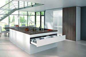 Projektanci nowoczesnych wnętrz kuchennych dążą do tego, aby zabudowa meblowa stanowiła jednorodną całość, chętnie więc wprowadzają duże płaszczyzny drzwi przesuwnych, którymi zastępują zlepek mniejszych modułów szafkowych. Rozwiązanie to sprawdzi się szczególnie w otwartych kuchniach. Fot. Hettich