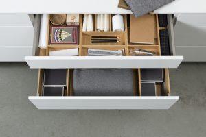 Długopis do rozwiązania krzyżówki, ulubiona gra czy podręczne drobiazgi, po które sięgamy podczas relaksu w salonie będą zawsze na swoim miejscu, jeżeli szuflady ArciTech wyposażymy w praktyczne organizery OrgaStore 230, które idealnie uporządkują ich wnętrze. Fot. Hettich