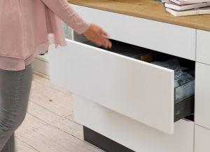 W nowoczesnych meblach salonowych można zrezygnować z uchwytów. Aby otworzyć szufladę wystarczy delikatnie nacisnąć jej front w dowolnym miejscu. Funkcja Push to open Silent odpowiada również za miękkie i bezpieczne domknięcie szuflady. Fot. Hettich