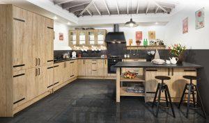 Postarzane fronty ze stylizowanymi okuciami w kuchni Kamelia doskonale komponują się z dekorem kamiennym w ciemnym wybarwieniu. Taki duet tworzy spójną stylistycznie kompozycję, a kuchnia zachwyca swojską urokliwością. Fot. KAM