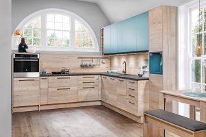 Zabudowę kuchenną z przewagą dekorów drewna można ożywić intensywnym akcentem kolorystycznym. Dla wzmocnienia efektu kolor jest również wprowadzony w otwartej półce, ciekawie wkomponowanej w bryłę mebli z systemu KAMplus. Fot. KAM