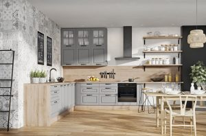 Otwarte półki, fronty z dekoracyjnymi frezowaniami i przeszkleniami oraz uniwersalna szarość połączone z dekorami drewna i utrzymane w stylistyce skandynawskiej to sprawdzony sposób na piękne i uniwersalne wnętrze, które oprze się upływowi czasu. Fot. KAM