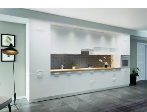 Jednolita zabudowa kuchenna mniej rzuca się w oczy, dzięki czemu, nawet w przypadku wysokich szafek w systemie KAMmono, nie zdominuje salonu. Fot. KAM