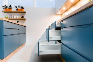 Zamiast uniwersalnych szafek możemy zaprojektować pakiet szuflad o różnych wysokościach, w których będą przechowywane pogrupowane przedmioty czy zapasy spożywcze. To prosty sposób, aby dopasować zabudowę meblową do konkretnych potrzeb użytkowników. Fot. KAM